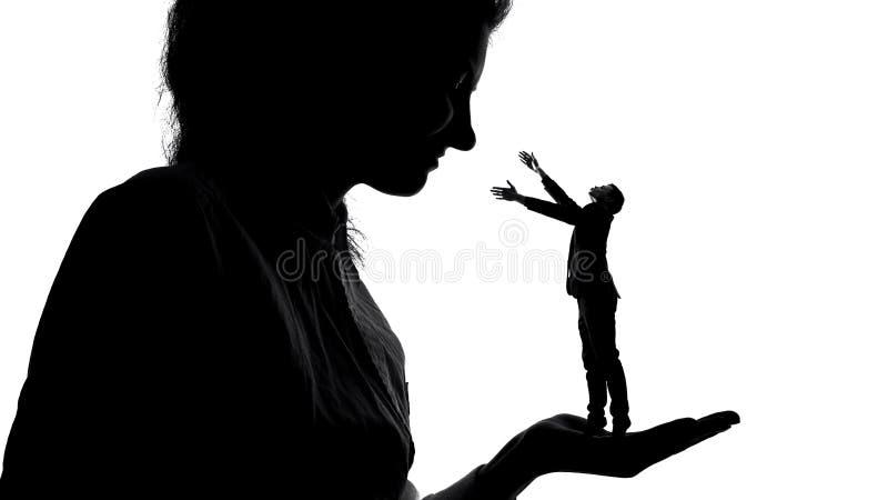 Schattenbild von Dame kleinen männlichen Bewunderer in der Hand halten, Frauenmacht, Herrschaft lizenzfreies stockfoto