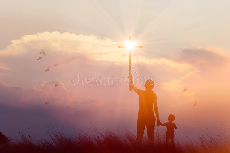Schattenbild von den christlichen Gebeten der Mutter und des Sohns, die Kreuz beim Beten zum Jesus auf Sonnenunterganghintergrund lizenzfreie stockbilder