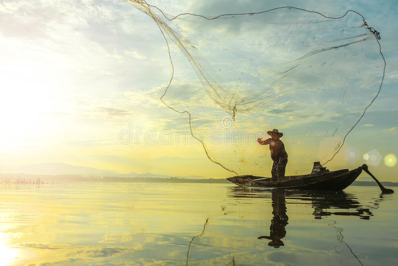 Schattenbild von den Fischern, die Korb ähnliches Blockierfangende Fische im See mit schöner Landschaft des Naturmorgensonnenaufg lizenzfreie stockbilder