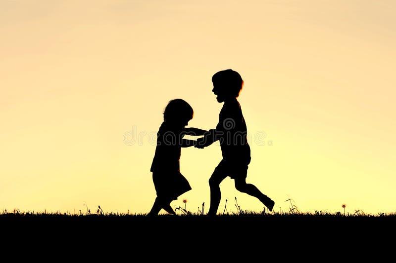 Schattenbild von den glücklichen kleinen Kindern, die bei Sonnenuntergang tanzen stockbild