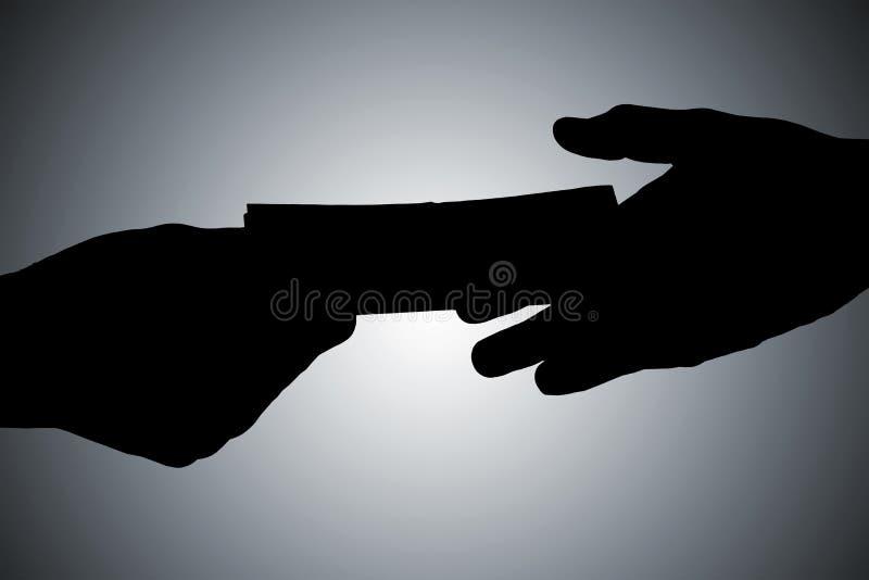 Schattenbild von den Händen, die Bestechungsgeld geben lizenzfreies stockfoto