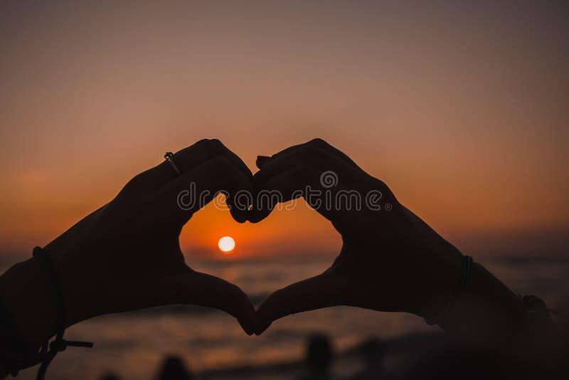 Schattenbild von den Händen, die Liebe bei Sonnenuntergang bedeuten stockbild