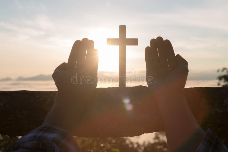 Schattenbild von den jungen menschlichen Händen, die mit einem Kreuz bei Sonnenaufgang, Christian Religions-Konzepthintergrund be stockfotografie