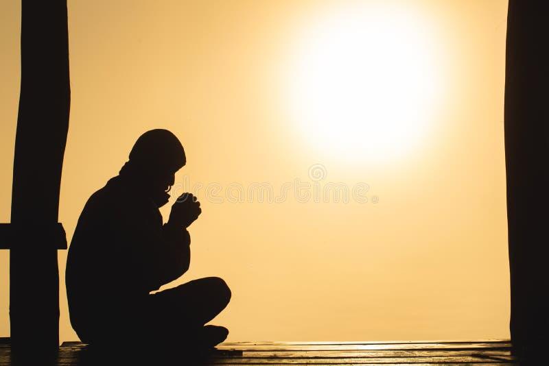 Schattenbild von den jungen menschlichen Händen, die zum Gott bei Sonnenaufgang, Christian Religions-Konzepthintergrund beten stockbild