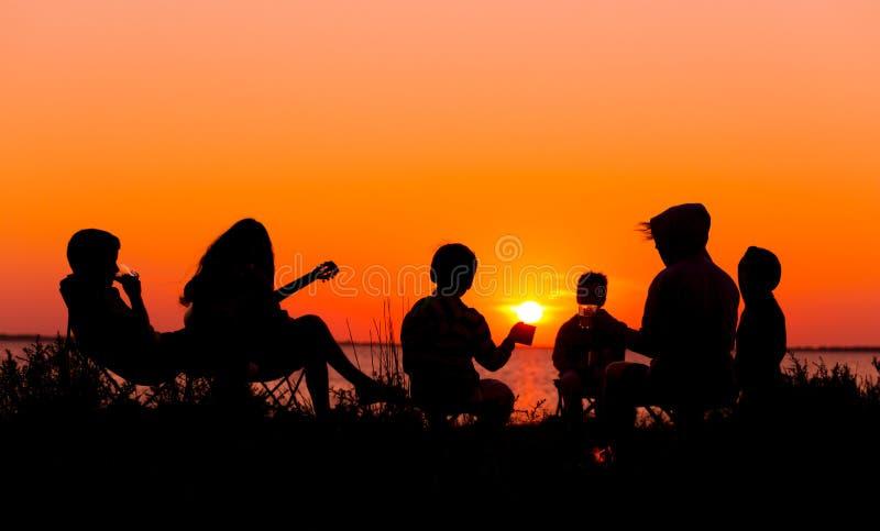 Schattenbild von den Leuten, die auf dem Strand mit Lagerfeuer am sunse sitzen stockfoto