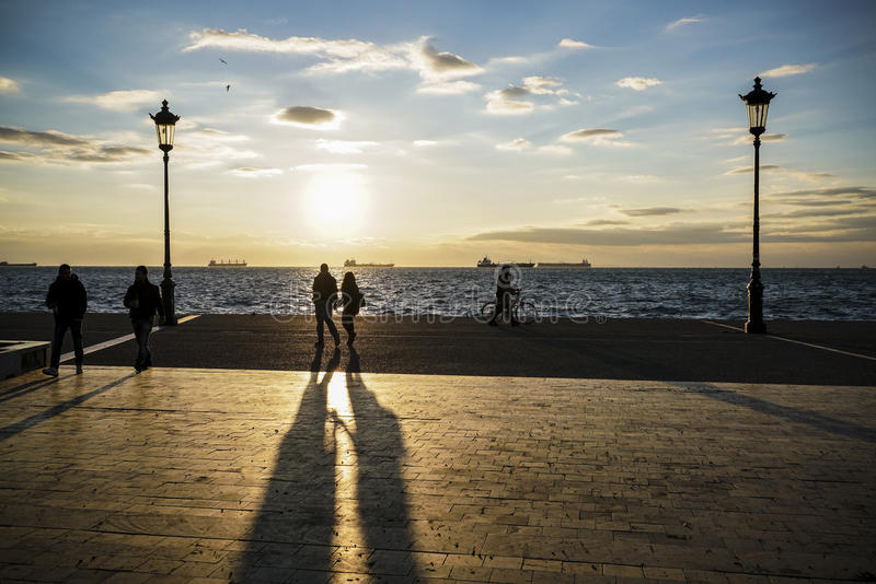 Schattenbild von den Leuten, die bei Sonnenuntergang durch Meer gehen stockfotografie