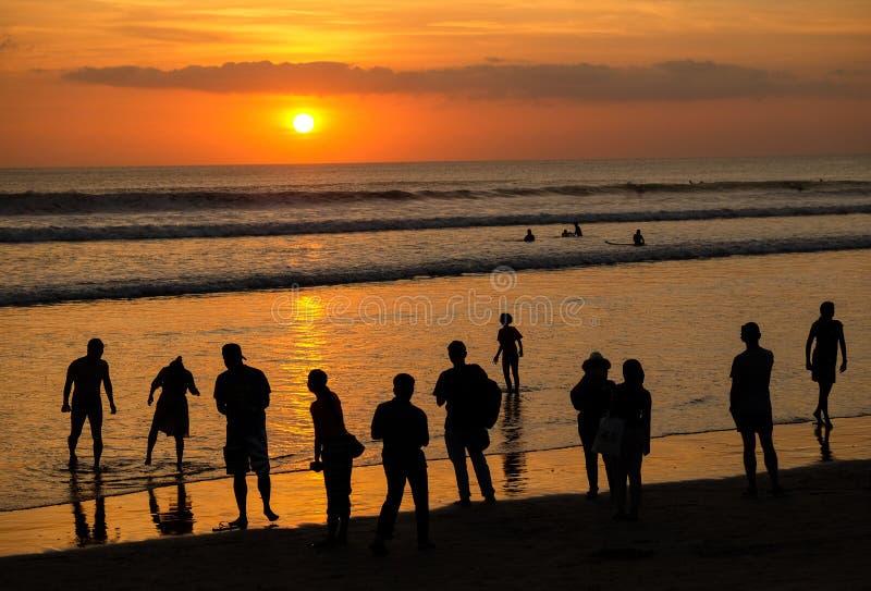 Schattenbild von den Leuten, die Sonnenuntergang auf Kuta-Strand, Bali betrachten lizenzfreie stockfotografie