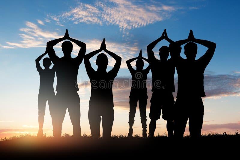 Schattenbild von den Leuten, die Yoga tun stockbilder