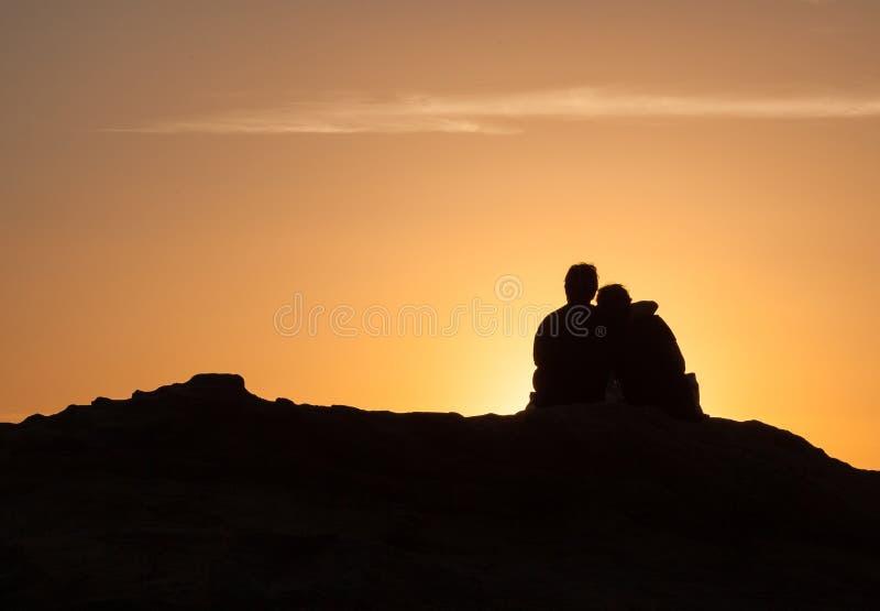 Schattenbild von den Paaren, die auf einem Felsen bei Sonnenuntergang sitzen lizenzfreie stockbilder