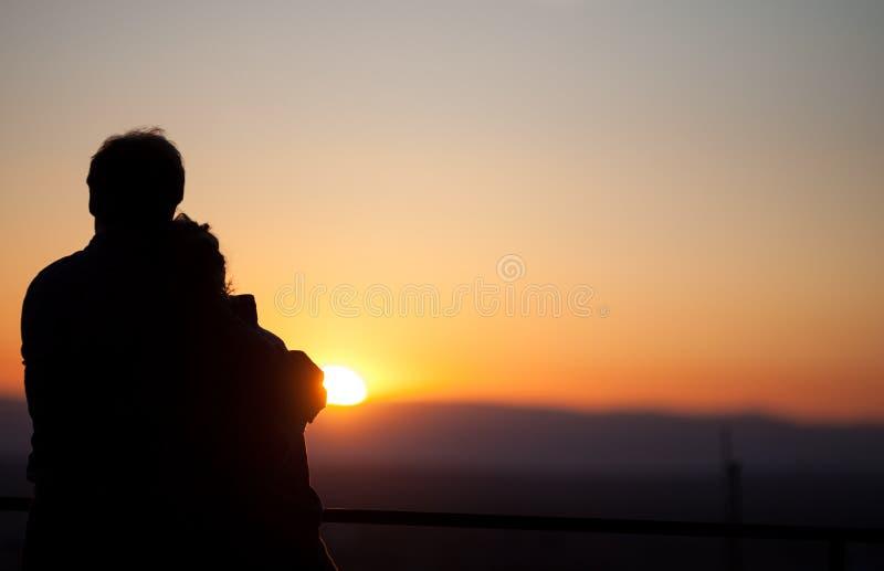 Schattenbild von den Paaren, die Sonnenuntergang über Freiburg, Deutschland genießen stockfoto