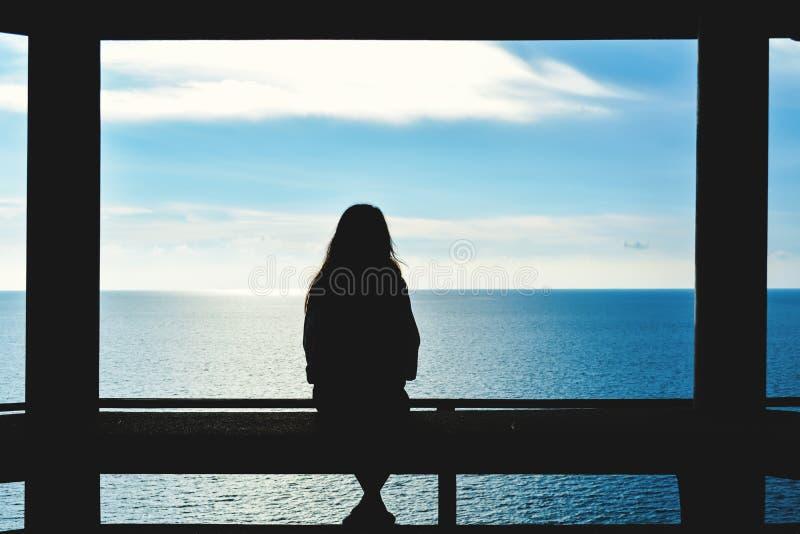 Schattenbild von den sitzenden Frauen und schauen das Meer lizenzfreie stockfotos