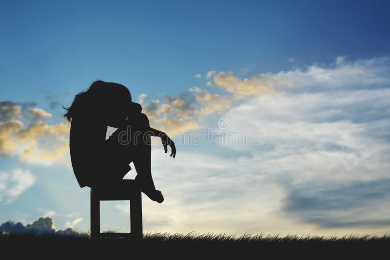 Schattenbild von den traurigen Frauen, die auf Stuhl sitzen lizenzfreie stockbilder