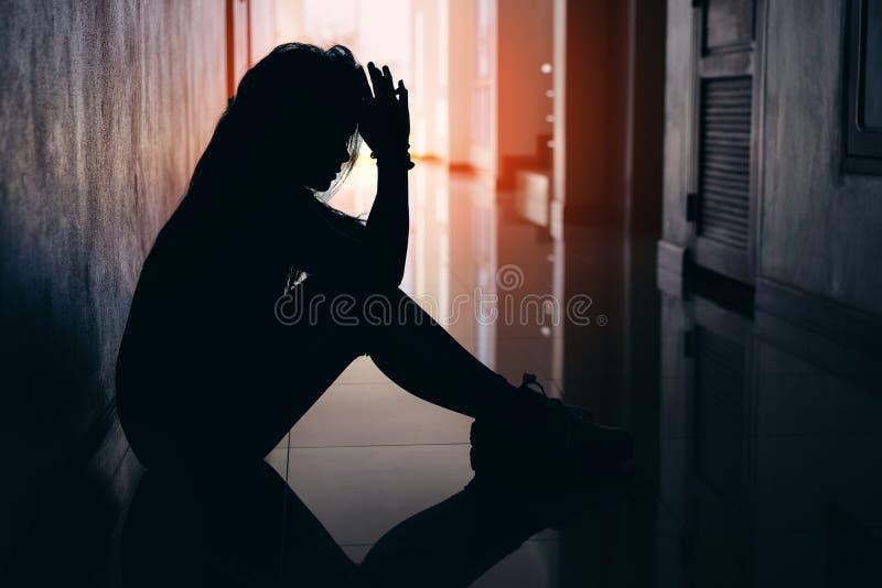 Schattenbild von den traurigen und deprimierten Frauen, die am Gehweg des Kondominiums oder des Büros sitzen lizenzfreies stockfoto