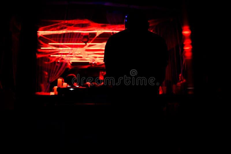 Schattenbild von einem DJ, das seine Konsole spielt stockfotos