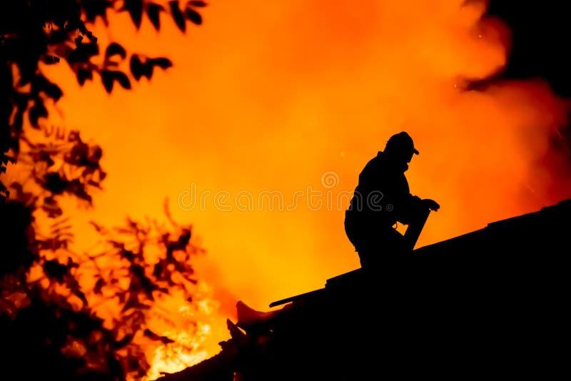 Schattenbild von Feuerwehrmännern auf dem Dach eines brennenden Hauses lizenzfreies stockbild