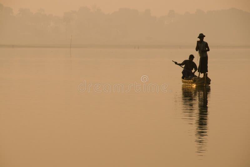 Schattenbild von Fischern im goldenen Morgenlicht mit einem Fußruderer, auf dem Taungthaman See auf Myanmar lizenzfreie stockfotos