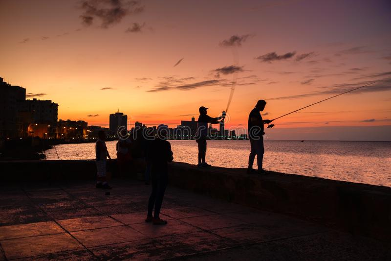 Schattenbild von Fischern und die Stadtskyline in Havana stockfotografie