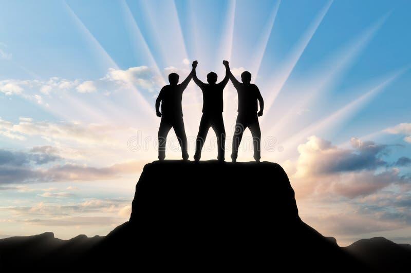 Schattenbild von glücklichen drei Bergsteigern auf die Oberseite lizenzfreies stockfoto