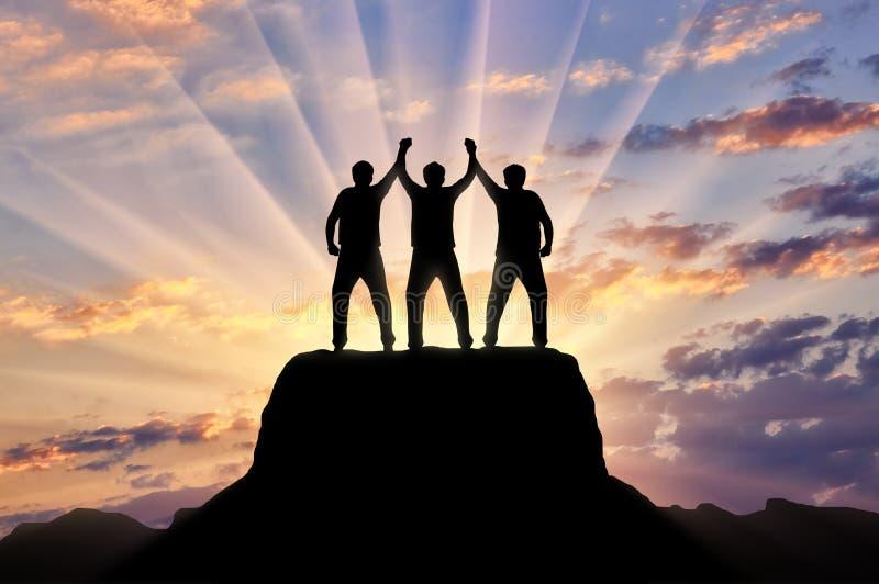 Schattenbild von glücklichen drei Bergsteigern auf die Oberseite des Berges stockbilder