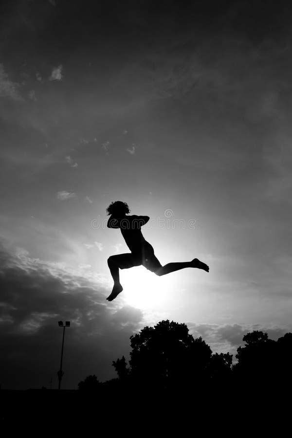 Schattenbild von Gymnast auf Trampoline im Himmel stockfoto