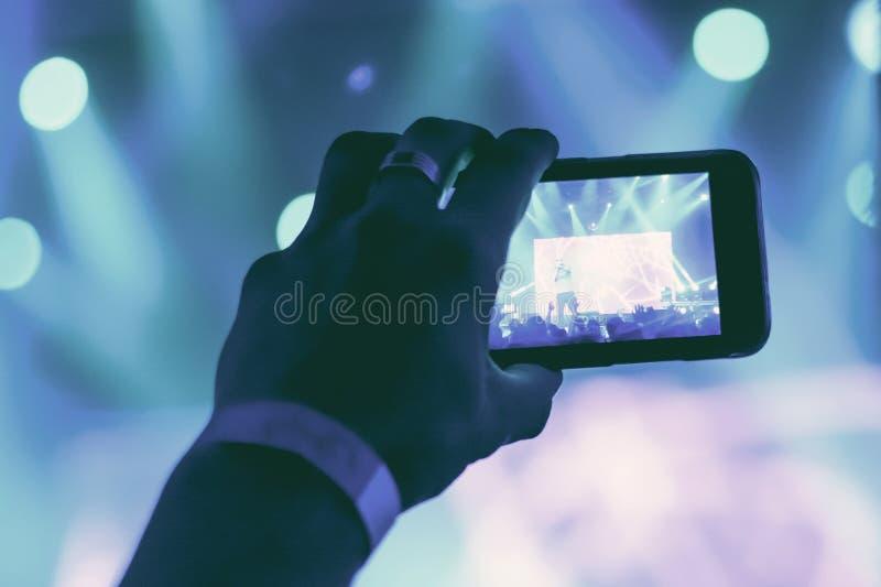 Schattenbild von Händen mit einem Smartphone an einem Konzert lizenzfreies stockbild