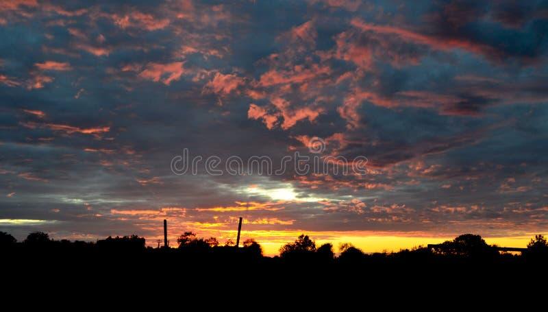 Schattenbild von Häuser mit einem blauen orange Himmel der Steigung während eines schönen Sonnenuntergangs im ländlichen Dorf von stockbilder