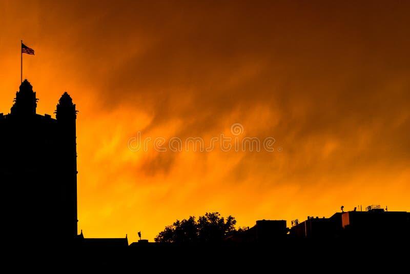 Schattenbild von Harlem-Skylinen, wenn die amerikanische Flagge in den Wind wellenartig bewegt, gegen einen hellen gelben brennen stockfotos