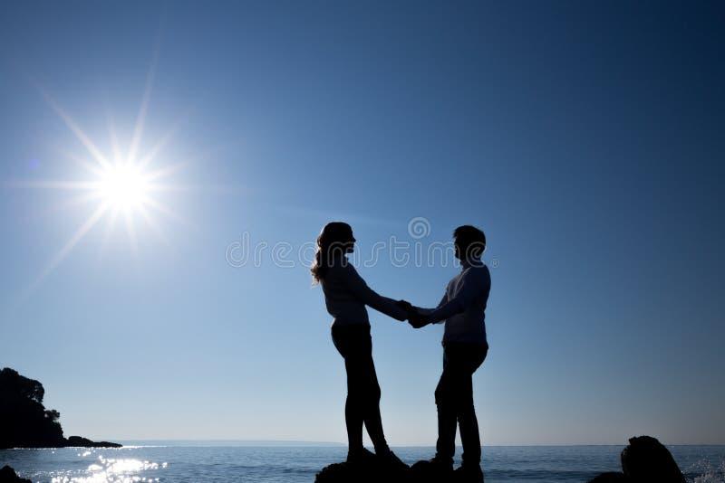 Schattenbild von Jugendlichpaaren auf dem Strand stockbild