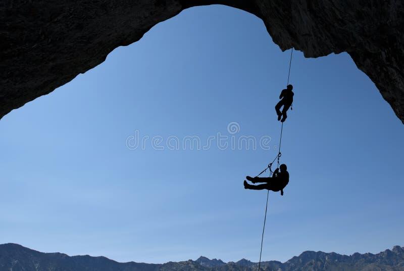 Schattenbild von Kletterern über Hintergrund des blauen Himmels stockbild