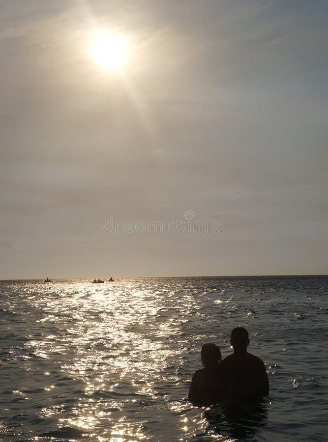 Schattenbild von Paaren von Liebhabern auf Kapstrand setzen auf den Strand lizenzfreie stockbilder