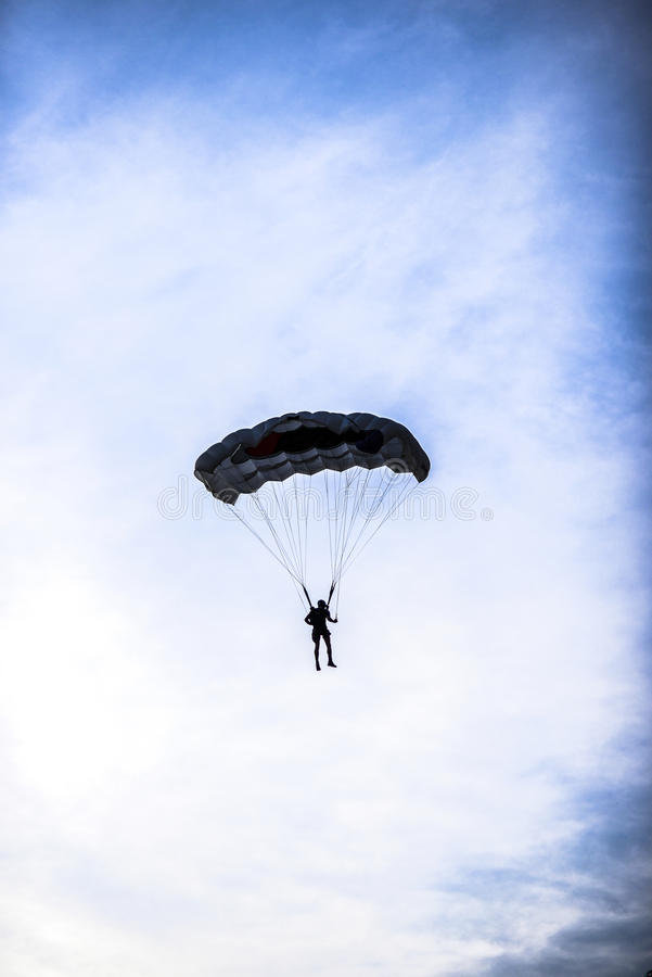 Schattenbild von parachuter auf einem blauen Himmel mit Wolken auf ihm lizenzfreie stockfotografie