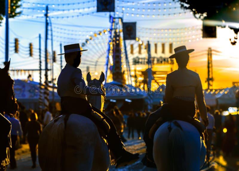 Schattenbild von Pferdereitern bei Sonnenuntergang Sevilla-` s April Fair Spanische Kultur lizenzfreie stockfotos