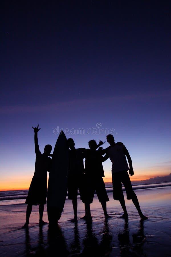 Schattenbild von vier Männern, die ein Surfbrett auf dem Strand anhalten lizenzfreies stockbild