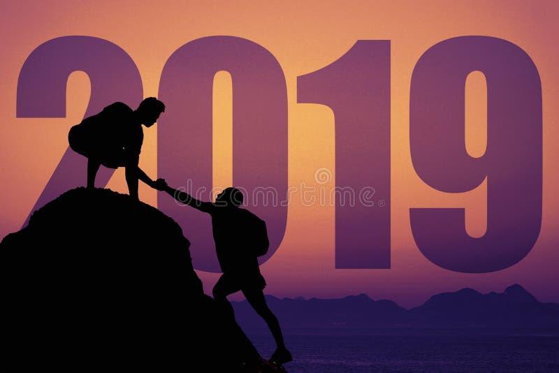Schattenbild von zwei Bergsteigern auf Bergspitze mit neuem Jahr 2019 stockfoto