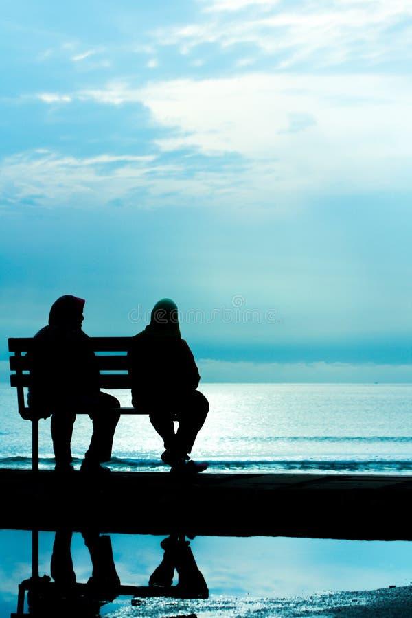 Schattenbild von zwei Freunden, die auf hölzerner Bank nahe Strand sitzen stockbild