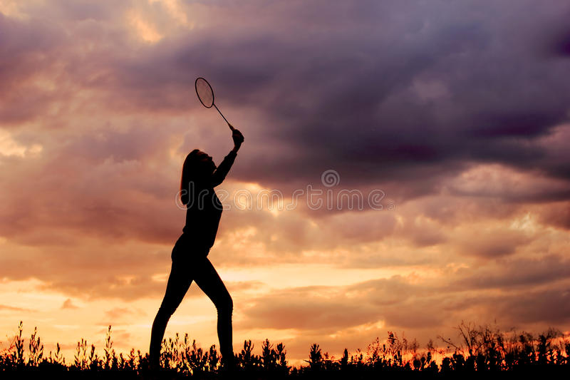 Schattenbildbadminton, das Mädchen auf Sonnenuntergang spielt lizenzfreies stockfoto