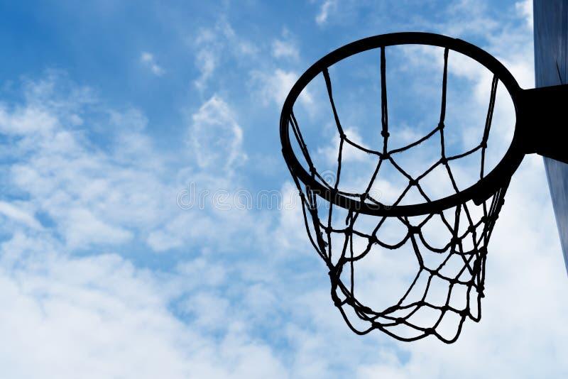 Schattenbildbasketballkorb mit blauem weißem Wolkenhimmel-Sporthintergrund stockbild