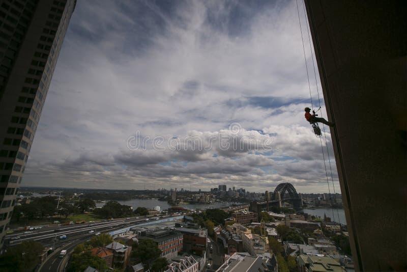 Schattenbildbild der Bauseil-Zugangsarbeitskraft, die einen Schutzhelm, vollen KörperSicherheitsgurt arbeitet auf der Höhe, absei lizenzfreie stockfotos