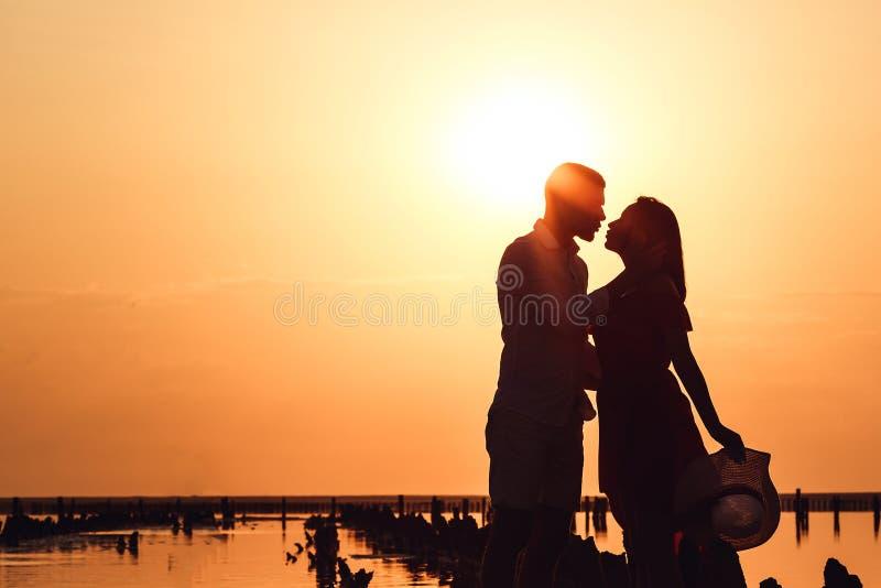Schattenbildbild eines liebevollen Paares, das bei Sonnenuntergang auf einem See umfasst stockfoto