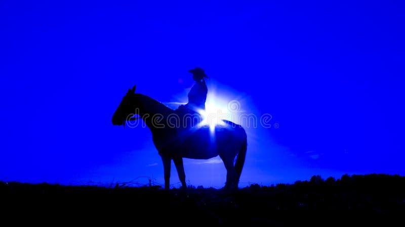 Schattenbildcowgirl auf Pferd bei Sonnenuntergang im Blau lizenzfreies stockbild