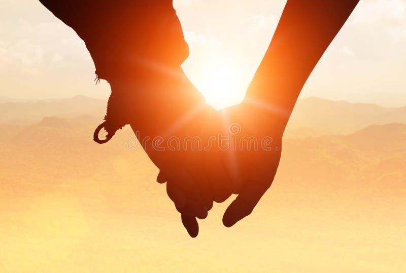 Schattenbilder auf Sonnenuntergang des liebevollen Paarhändchenhaltens während walki stockfotografie