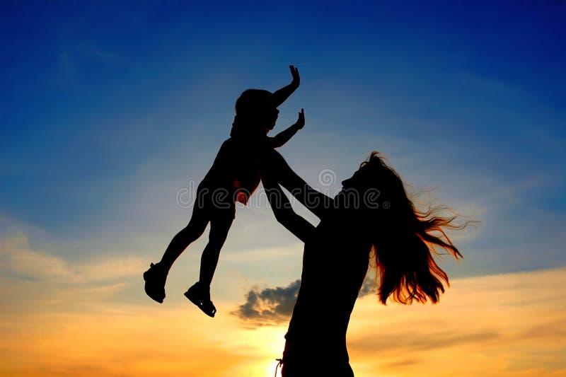 Schattenbilder bemuttern und Kind auf Sonnenuntergang lizenzfreies stockfoto