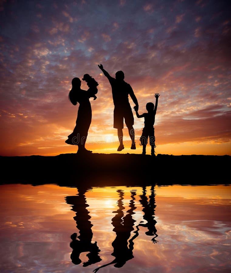Schattenbilder der glücklichen Familie auf der Seeküste stockfoto