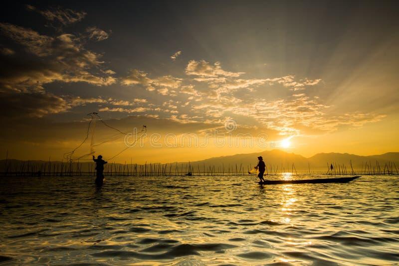 Schattenbilder der traditionellen Fischer, die Fischernetz DU werfen stockbilder