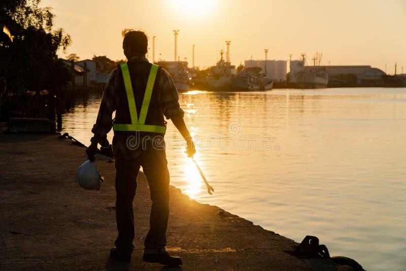 Schattenbilder des asiatischen Manningenieurs, der Schl?ssel h?lt und auf Werft und Hintergrund steht, ist ?l-Speicherung Silo lizenzfreies stockfoto