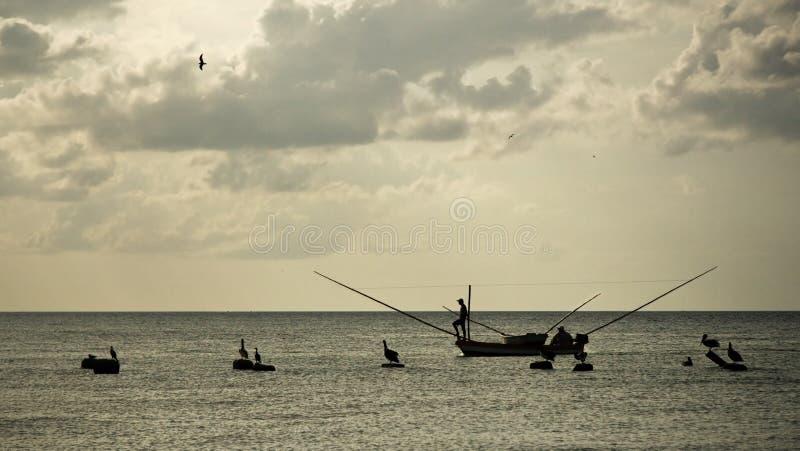 Schattenbilder des Fischers auf kleinem Fischerboot, mit neotropic c lizenzfreie stockfotos