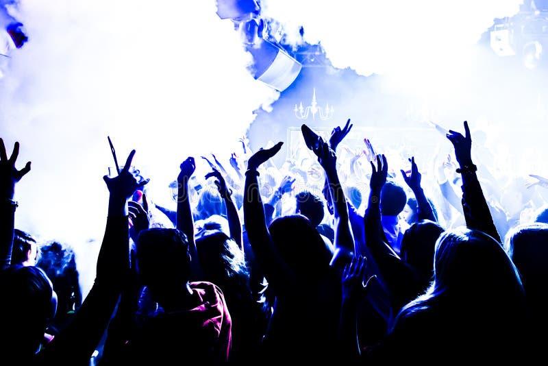 Schattenbilder des Konzertpublikums vor hellem Stadium beleuchtet mit Konfettis lizenzfreie stockfotografie