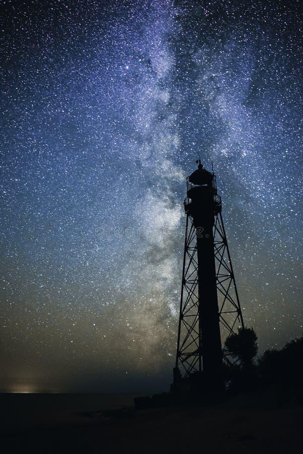 Schattenbilder des sandigen Strandes des alten Leuchtturmes und des Ozeans vor dem hintergrund des sternenklaren Himmels lizenzfreie stockbilder