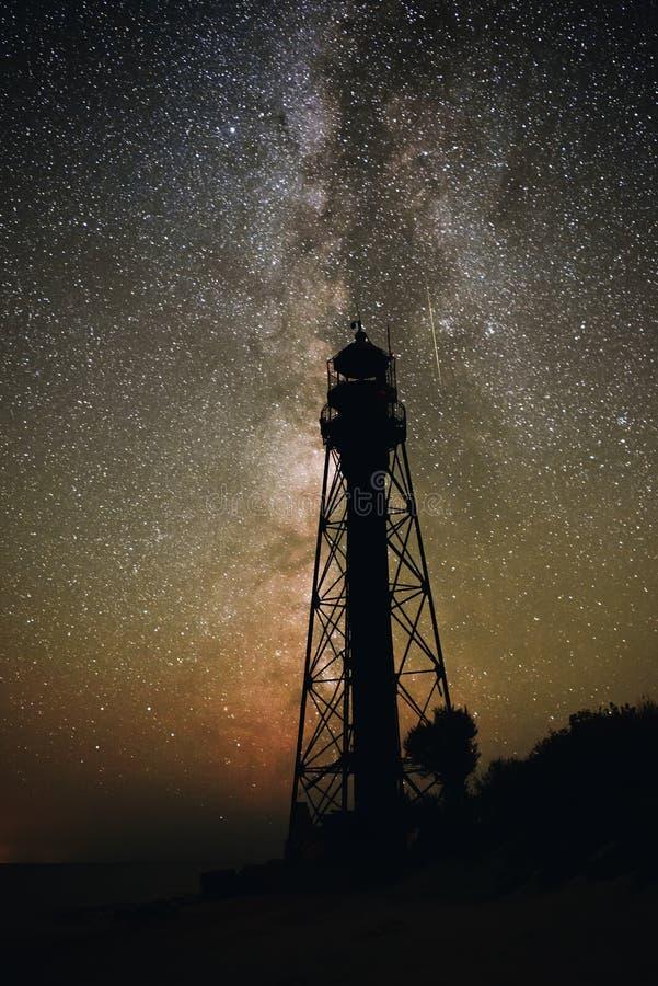 Schattenbilder des sandigen Strandes des alten Leuchtturmes und des Ozeans vor dem hintergrund des sternenklaren Himmels stockbilder