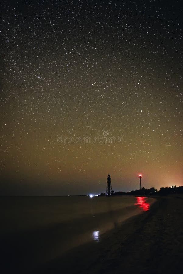 Schattenbilder des sandigen Strandes mit zwei Leuchttürmen und des Ozeans vor dem hintergrund des sternenklaren Himmels lizenzfreie stockfotografie